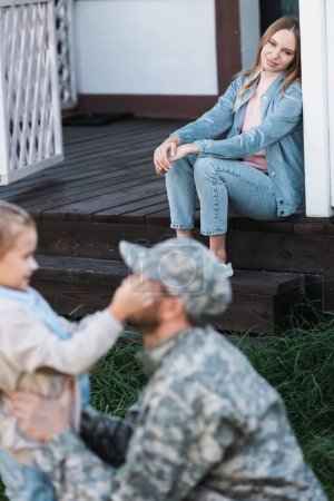 Photo for Smiling woman sitting on house threshold with blurred military serviceman and daughter on foreground - Royalty Free Image
