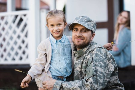 Photo for Happy daughter and father in military uniform hugging and looking at camera with blurred woman and house on background - Royalty Free Image