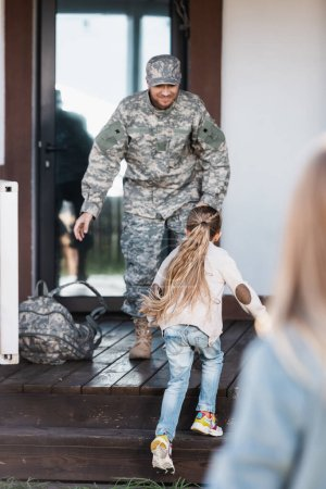 Photo pour Petite fille courant vers l'homme militaire debout sur le seuil de la maison avec une femme floue au premier plan - image libre de droit