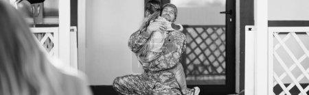 Photo pour Père en uniforme militaire embrassant fille, assis sur le genou près de la porte arrière avec femme floue au premier plan, bannière, monochrome - image libre de droit
