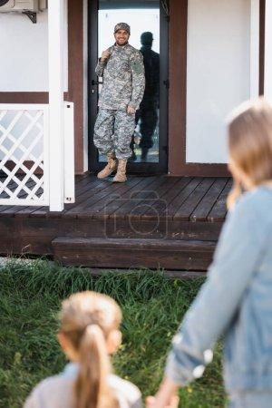 Photo pour Joyeux militaire militaire debout près de la porte arrière sur le seuil avec femme floue et fille au premier plan - image libre de droit
