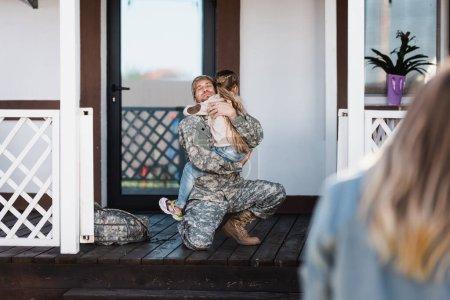 Photo pour Homme de service militaire souriant embrassant sa fille, assis sur le genou sur le seuil avec une femme floue au premier plan - image libre de droit