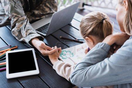 Photo pour Fille assise à table, dessin, tenant la main avec son père à la maison - image libre de droit