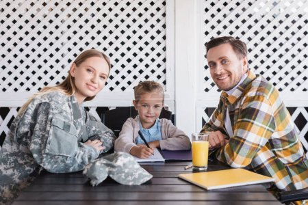 Smiling girl with man in checkered shirt and woman in military uniform sitting at table with notebooks, banner