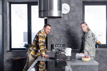 Lächelnde Männer und Frauen in Militäruniform blicken in die Kamera, während sie sich in der Loftküche auf den Tisch lehnen