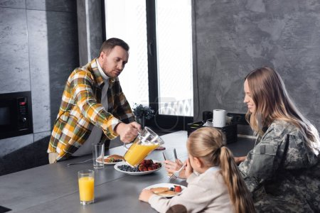 Adult man pouring glass with juice near military woman and girl eating pancakes with fruits in kitchen