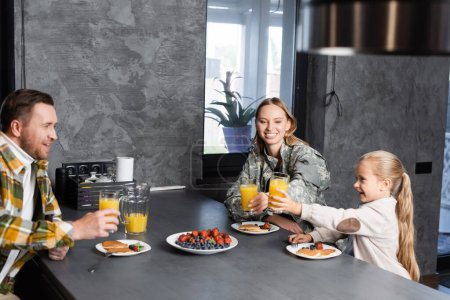Photo for Happy family toasting with glasses of juice, while sitting at table with fruits and pancakes in kitchen - Royalty Free Image