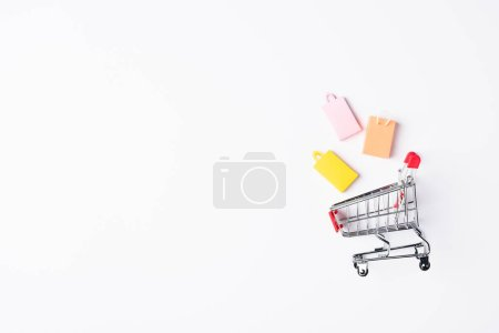 Top view of toy shopping bags near cart on white background