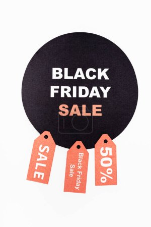 Photo for Top view of black circle with black friday lettering near price tags on white background - Royalty Free Image