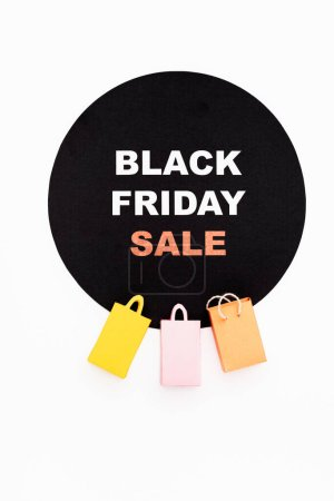 Top view of colorful toy shopping bags near black circle with black friday lettering on white background