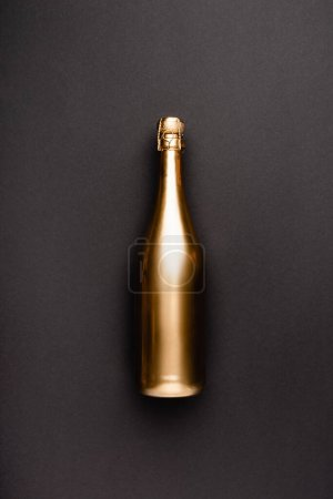 Photo for Top view of golden bottle of champagne on black background - Royalty Free Image