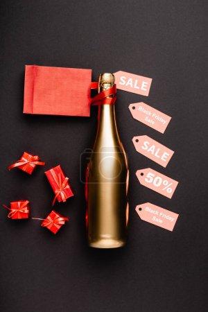 Draufsicht auf goldene Flasche Champagner in der Nähe von Preisschildern und Spielzeuggeschenken auf schwarzem Hintergrund