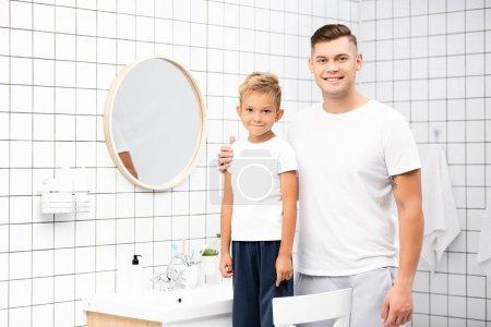 Photo pour Père souriant étreignant son fils debout sur la chaise près du miroir et évier dans la salle de bain - image libre de droit