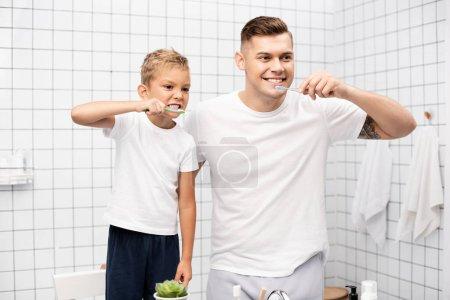 Foto de Padre e hijo mostrando dientes y sosteniendo cepillos de dientes, mientras mira hacia otro lado en el baño - Imagen libre de derechos