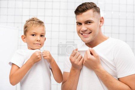 Photo pour Souriant père et fils tirant des t-shirts blancs tout en regardant la caméra dans la salle de bain - image libre de droit