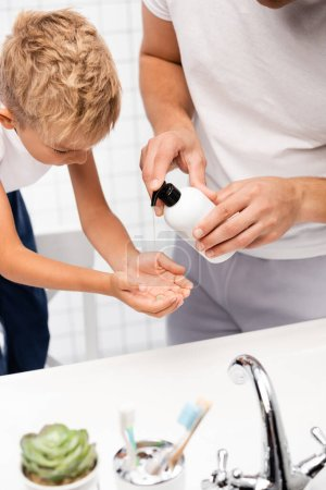 Vater drückt Flüssigseife auf die Hand des Sohnes, der sich nach vorne lehnt, während er im Badezimmer auf einem Stuhl im verschwommenen Vordergrund steht