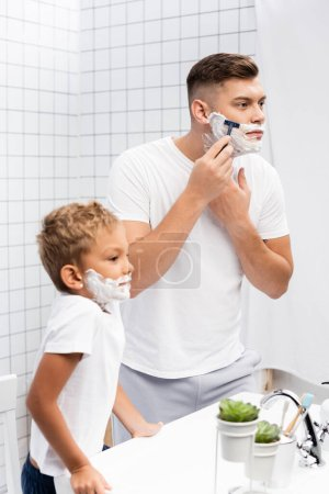 Boy with shaving foam on face leaning on sink while standing near man using safety razor in bathroom