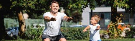 Photo pour Fils avec les mains tendues regardant père en vêtements de sport accroupi dans le parc sur fond flou, bannière - image libre de droit