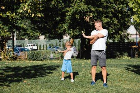 Photo pour Père et fils en tenue de sport s'échauffent avant de s'entraîner au parc - image libre de droit