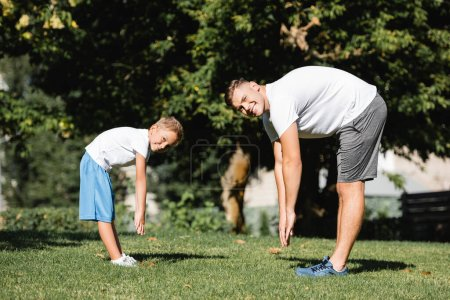 Photo for Happy man and boy looking at camera, while stretching in park with blurred trees on background - Royalty Free Image