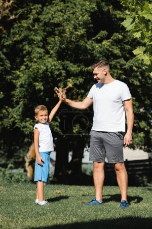 Photo for Preschooler boy in sportswear looking at camera while giving high five to smiling man in park - Royalty Free Image