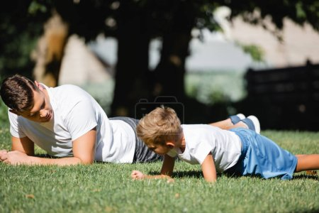 Father and son in sportswear doing plank on grass in park on blurred background