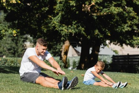 Father and son in sportswear with outstretched hands warming up, while sitting on grass on blurred background