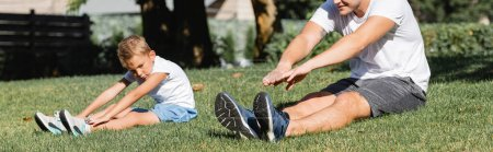 Preschooler boy with outstretched hands warming up while sitting near young adult man in park on blurred background, banner