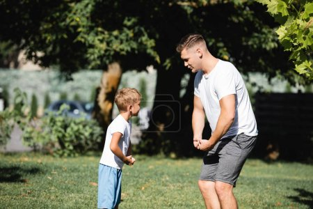 Son and father in sportswear showing muscles in park on blurred background