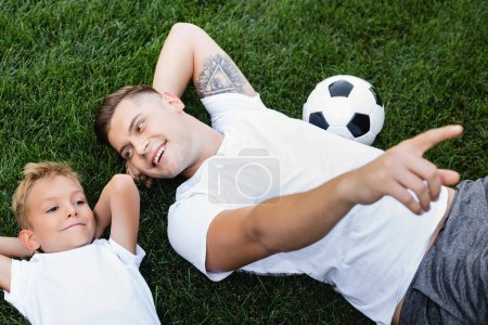 Overhead view of happy father pointing with finger, while looking at smiling son lying with hands behind head on grass