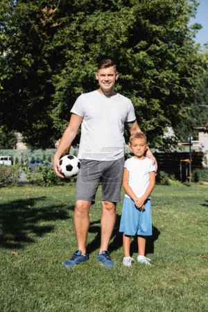 Smiling man in sportswear with ball embracing preschooler boy with clenched hands in park