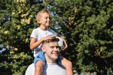 Photo for Smiling son with ball riding piggyback on happy father in park on blurred background - Royalty Free Image