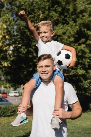 Happy son with hand in air holding ball, while riding piggyback on smiling father in park on blurred background