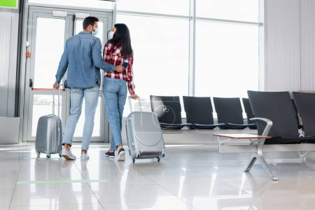 Photo for Back view of multicultural couple walking with luggage in airport - Royalty Free Image