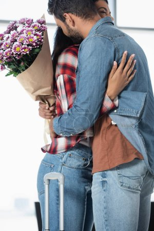 Photo for Man holding wrapped flowers while hugging african american girlfriend in airport - Royalty Free Image