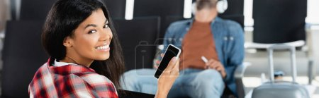 happy african american woman holding smartphone with blank screen near man on blurred background, banner