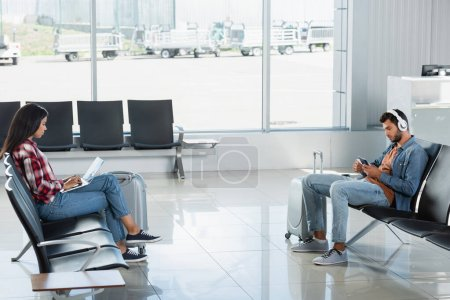 man in headphones holding passport near african american woman using laptop in departure lounge of airport