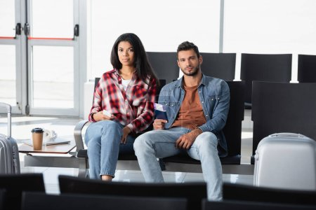 interracial passengers holding passports with air tickets in airport