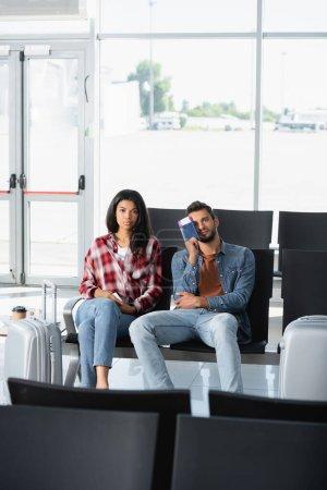 Photo pour Passagers interracial titulaires d'un passeport avec carte d'embarquement à l'aéroport - image libre de droit