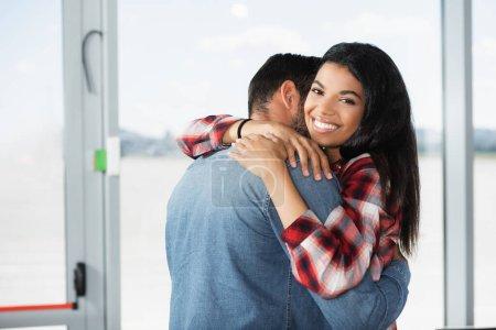 cheerful african american woman hugging boyfriend in airport