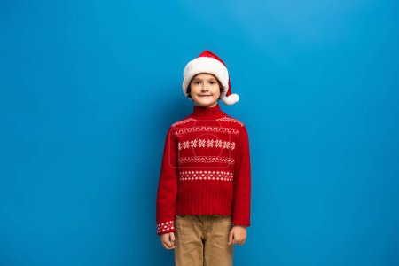 Photo for Happy boy in santa hat and red knitted sweater looking at camera on blue - Royalty Free Image
