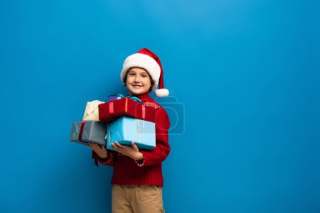 Photo for Happy boy in santa hat and sweater holding presents on blue - Royalty Free Image
