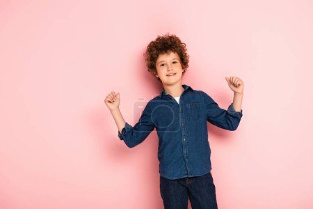 excited curly boy with clenched fists standing on pink