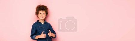 Photo pour Récolte panoramique de garçon joyeux et bouclé montrant pouces isolés sur rose - image libre de droit