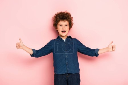 joyful and curly boy with outstretched hands showing thumbs up on pink