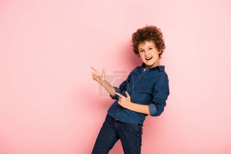 excited curly boy in denim shirt pointing with fingers on pink