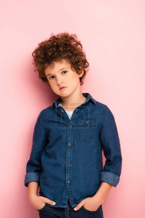 Photo for Serious and curly boy looking at camera on pink - Royalty Free Image
