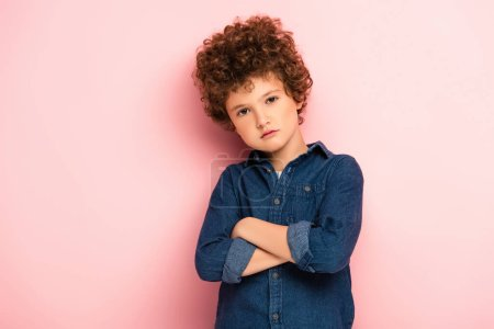 Photo for Serious and curly boy standing with crossed arms on pink - Royalty Free Image