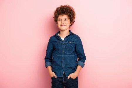 Photo pour Garçon heureux et bouclé en denim chemise debout avec les mains dans les poches sur rose - image libre de droit