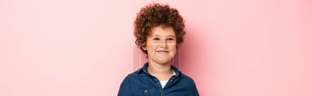 panoramic crop of pleased and curly boy in denim shirt smiling on pink